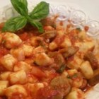 Rossi's Sausage Gnocchi - Tender gnocchi pasta is served in a homemade tomato sauce with slices of Italian sausage and topped with grated Romano cheese.