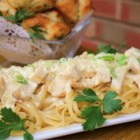 Creamy Chicken on Linguine - Tender strips of chicken browned in oil, butter and garlic are arranged over hot pasta and topped with a sumptuous sauce of cream, milk, onions, scallions and Parmesan cheese.