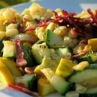 Corn and Zucchini Melody - Zucchini, corn, and onions are cooked in a skillet and topped with crispy crumbled bacon and shredded Monterey Jack cheese.