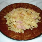 Easy Ham and Noodles - Leftover ham gets a second chance to please your palate in this simple casserole of egg noodles, Cheddar cheese and cream of mushroom soup. Add sweet green peas for color and flavor.