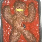 "Halloween Halfling Meatloaf - A Halloween meatloaf is decorated like a spooky Halfling -- a mysterious humanoid creature with yellow corn teeth, green pepper ears, black olive eyeballs, and a background of scary ""blood"" ketchup."