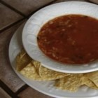 Easy Tortilla Soup - A Mexican-inspired soup that is made by starting with a can of chicken and rice soup. Diced tomato with green chilies, and tomato sauce are stirred into the coup creating a creamy and potent combination. Tortilla chips are placed in individual soup bowls