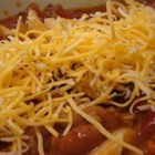 Chili with Ziti - Spicy chili with ground beef, onion, garlic, and kidney beans simmered in tomato sauce. Seasoned with oregano and cinnamon. Served over ziti pasta and topped with Cheddar cheese.