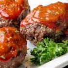 Mini Meatloaves - A meatloaf mixture of ground beef, cheese, and quick-cooking oats is formed into individually sized loaves. They are glazed with a sauce of ketchup, brown sugar, and mustard.