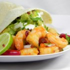 Chipotle Shrimp Tacos - Warm corn tortillas filled with spicy chipotle shrimp and garnished with cilantro, onion, and lime.