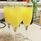Holiday Mimosa - Serve up these festive champagne and orange juice classics in glasses rimmed with orange liqueur and sugar.
