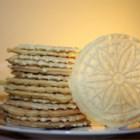 Pizzelles III - This recipe calls for a batter-like dough and is baked on a pizzelle iron. Powdered sugar adds an elegant touch. In the Italian version, vanilla is replaced by anise. Chocolate may also be used.