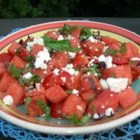 Watermelon and Tomato Salad - Cubes of watermelon and cherry tomato halves are tossed with crumbled feta cheese, basil, and lemon zest in this refreshing salad.