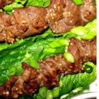 Bo Nuong Xa - Traditional Vietnamese ingredients flavor this marinated beef, which is broiled or grilled on skewers and served over romaine lettuce leaves. It is garnished with fresh basil, green onions, and mint.