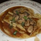 Egg Foo Yung with Mushroom Sauce - These egg and bean sprout pancakes are cooked in peanut oil, and bathed in mushroom sauce.