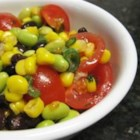 Healthy Garden Salad - Edamame, corn, cherry tomatoes, and black beans combine to make a colorful salad with a light lime vinaigrette dressing.