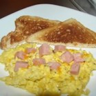 Spam and Eggs - Cubes of Spam are fried in a skillet with eggs, and topped with cheese.
