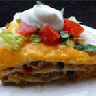 Burrito Pie - Ground beef, refried beans and tomatoes are combined with chiles and taco sauce, then  layered in a casserole with tortillas and cheese, and baked.