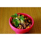 Southwestern Black Bean Stew - Browned ground beef seasoned with a package of taco seasoning mix is combined with whole kernel corn and canned black beans in this stew served with a dollop of sour cream and grated cheddar cheese.