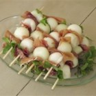 Prosciutto Wrapped Melon Balls - This is a great snack to make for any gathering. Balls of honeydew melon are wrapped in prosciutto and fresh mint to make a fancy appetizer with few ingredients.