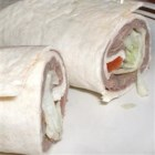 Mexican Roll Ups - A tasty alternative to sandwiches for a lunchbox or picnic. Roast beef, chopped tomatoes, bell peppers, and seasonings are rolled in whole wheat tortillas and wrapped in tinfoil. East to transport, and neat to eat.