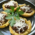 Tostones Rellenos (Stuffed Plantain Cups) - Plantains are gently fried, then smashed and shaped into cups and fried again. The crispy cups are then filled seasoned beef and topped with cheese in this impressive dish.