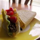 American Turkey Tacos - Seasoned ground turkey is piled onto warm taco shells, slathered with avocado and sour cream, and topped with pico de gallo and Colby cheese.