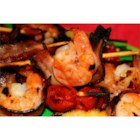 Hawaiian Shrimp - Shrimp, pineapple, bacon, cherry tomatoes, and mushrooms are skewered and grilled with a sweet and sour basting sauce for a tropical touch at any barbeque.