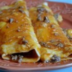Beef Enchiladas II - Simple and quick beef enchiladas. Ground beef and onion are wrapped in flour tortillas, topped with Cheddar cheese and black olives, then baked. This is also great with leftover chicken, shredded beef or turkey. Serve with a green salad or beans and rice.