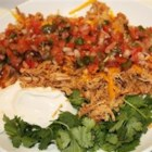 Mexican Style Shredded Pork - This is an amazing shredded pork recipe similar to what you would eat in a rice bowl (or in an enchilada) at a Mexican restaurant. It is easy to prepare and simmers in a slow cooker all day, ready to enjoy when you arrive home. I serve it over rice (laced with lime juice and fresh cilantro), Cheddar cheese, salsa, guacamole, and a dollop of sour cream. Amazing!