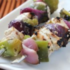 Marinated Greek Chicken Kabobs - Chicken pieces are marinated in a blend of yogurt , lemon juice, and feta, then grilled on skewers with onions and green peppers.