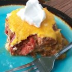 Taco Lasagna - A baked taco-style lasagna with layers of corn tortillas, salsa, seasoned ground beef and sour cream Topped with Cheddar and Monterey Jack cheeses.