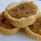 Pecan Pie Tarts -  These dainty treats are so easy to accomplish. The cream cheese pastry is mixed, rolled into balls and each pressed into the bottom and sides of tiny tart pans. The pecan filling is spooned in and the pies baked until the filling is set. Garnish each with a dollop of whipped cream and a pecan half.