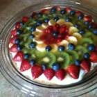 Fruit Pizza II - A baked cookie crust is spread with cream cheese and whipped topping, and fresh fruit is spiraled onto the top. A sweetened, citrus glaze is then spooned over the fruit. Chill this sweet pizza before serving.