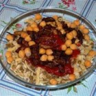 Egyptian Koshary - Rice, lentils, macaroni, browned onions, and tomato sauce are prepared separately, then spooned in layers on servings plates in this traditional Egyptian vegetarian meal.