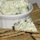 Pesto Herb Spread - This is a yummy, creamy version of standard pesto that makes a great spread for get togethers. Tastes great with pita chips or sourdough bread! Sun dried tomatoes may be mixed in for a zesty tang. Add crunch by coating the finished spread with almonds.