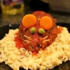 Halloween Bloody Baked Rats - This is a fun, inexpensive, creepy Halloween entree that will gross out and impress your dinner guests. It is  mini meatloaves baked in tomato sauce that are shaped like rats with cheese in the middle. When you cut  it open, gooey cheese will come oozing out. Garnished with a spaghetti noodle tail and carrot ears, these pests are sure to be a devilishly delectable dinner.