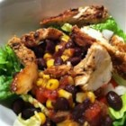 Chicken Fiesta Salad - Salad greens, onions and tomatoes are topped with Mexican flavored black beans, corn, and grilled chicken breasts. This is an attractive and zesty all in one dish.