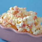 Candy Cane Popcorn - Popcorn mixed with white candy coating and crushed peppermint candy canes makes a quick, simple treat that's a little different for the cookie tray. Package it up in a pretty cellophane bag for a sweet gift. This recipe uses an air popper to make popcorn without added oil.