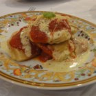 Homemade Four Cheese Ravioli - Fresh pasta filled with ricotta cheese, cream cheese, mozzarella cheese, and provolone cheese is drizzled with marinara sauce and finished with a pesto-Alfredo cream sauce.