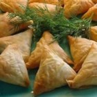 Tiropetes - Straight from Athens! Feta and Monterey Jack cheeses are mixed into a sauce with parsley and used to fill phyllo triangles in this delicious Greek appetizer.