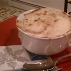 French Onion Soup IX - Thickly sliced onions are slowly cooked in butter, then combined with beef broth and Romano cheese before being ladled into bowls, and topped with toast and cheese.