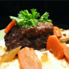 Smothered Beef Short Ribs - The flour-dredged ribs are browned in olive oil and then simmered with vegetables and herbs in red wine and beef stock.