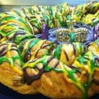 Super Easy Mardi Gras King Cake - Prepared sweet roll dough and colorful frostings speed up the cake baking process for a Mardi Gras King Cake. A small plastic baby inserted into the side of the cake will bring good luck in the coming year to whoever discovers it in their slice.