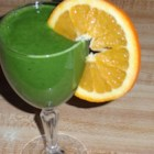 Kale Orange Banana Smoothie - A fresh orange, a pair of ripe bananas, and a kale leaf are blended into a pudding-like smoothie for a wholesome breakfast drink.