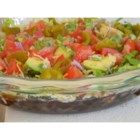 Manda's Seven Layer Taco Dip - A classic and fresh layered dip has refried black beans, fresh tomatoes and avocados, and salsa, all topped with cheese, lettuce, and pickled jalapenos. Bring lots of chips!