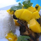 Grilled Chicken with Fresh Mango Salsa - A garlic and mango salsa tops grilled chicken breasts in this recipe for the perfect barbequed meal!