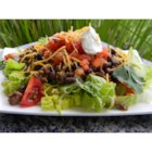 Easy Black Bean Taco Salad - Seasoned ground beef and black beans form the basis of a hearty taco salad with layers of lettuce, salsa, Mexican cheese blend, and sour cream and topped with tortilla chips.