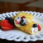 Cheesecake Crepe Roll-Ups - Tender, thin crepes are rolled up with berry-flavored cream cheese, sliced into pinwheels, and served cold. Just perfect for a breakfast in bed, Mother's Day, or to treat your valentine.