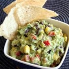 Corn and Black Bean Guacamole - This chunky guacamole has red pepper, corn, red onion, and black beans for a colorful dip for tortilla chips.