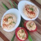 Smoked Salmon Deviled Eggs and Tomatoes - An enticing, pretty appetizer plate combines salmon-stuffed deviled eggs and stuffed cherry tomatoes. The treats get a sprinkling of smoked paprika to kick up the flavor and color.