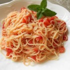 Tomato and Garlic Pasta - Bright red tomatos are peeled and chopped and cooked very briefly with tomato paste and sauteed garlic to make a fresh and colorful sauce for hot pasta. Stir in fresh basil just before combining the sauce with the pasta, then top with Parmesan cheese.