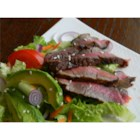Grilled Steak Salad with Asian Dressing - Seasoned rib eye steak is grilled to a tender medium-rare and served sliced over a colorful salad of romaine, avocado, carrot, and cucumber. The spicy rice vinegar dressing adds a tangy Asian-style flavor.