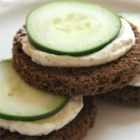 Cucumber Sandwich Appetizers - Pumpernickel party bread is spread with an Italian-inspired cream cheese and topped with thin slices of cucumber in this quick and easy appetizer.