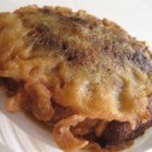 Sweet Plantain Pie - Layers of mashed plantain sweetened with sugar surround a filling of ground pork and ham with olives and capers in this Puerto Rican recipe.